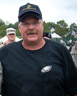 Color head-and-shoulders photograph of stocky white man (Andy Reid) wearing a dark green Philadelphia Eagles sweatshirt and a navy blue baseball cap with gold U.S. Marine Corps logo.