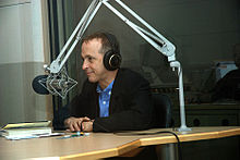 A man with headphones sits at a desk and leans towards a large microphone