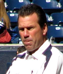 Color head-and-shoulders photograph of white man with dark (Gary Kubiak), wearing a white and navy sport shirt,  squinting in bright sunlight, with stadium seating in the background.