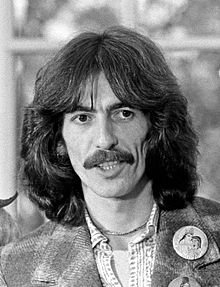 Black-and-white shot of a man in his early thirties, George Harrison, with mustache and long, dark hair.