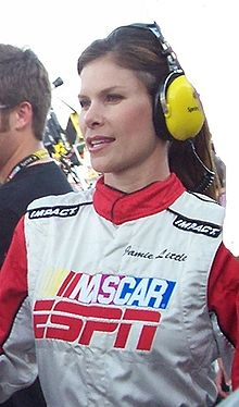 Dressed in a NASCAR/ESPN race reporter uniform, wearing a headset