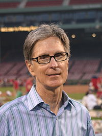 A portrait shot of a merry looking middle-aged Caucasian male (John W. Henry) looking straight ahead. He has short greying hair, and is wearing a blue-striped shirt with the top button open. In the background is a baseball stadium.