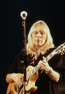 A blonde-haired woman stands in front of a microphone holding a guitar.