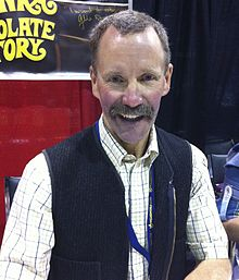 A middle-aged caucasoid man looking at the photographer; he is presented as a bust, wearing a yellow-plaid collared shirt under a cardigan sweater.